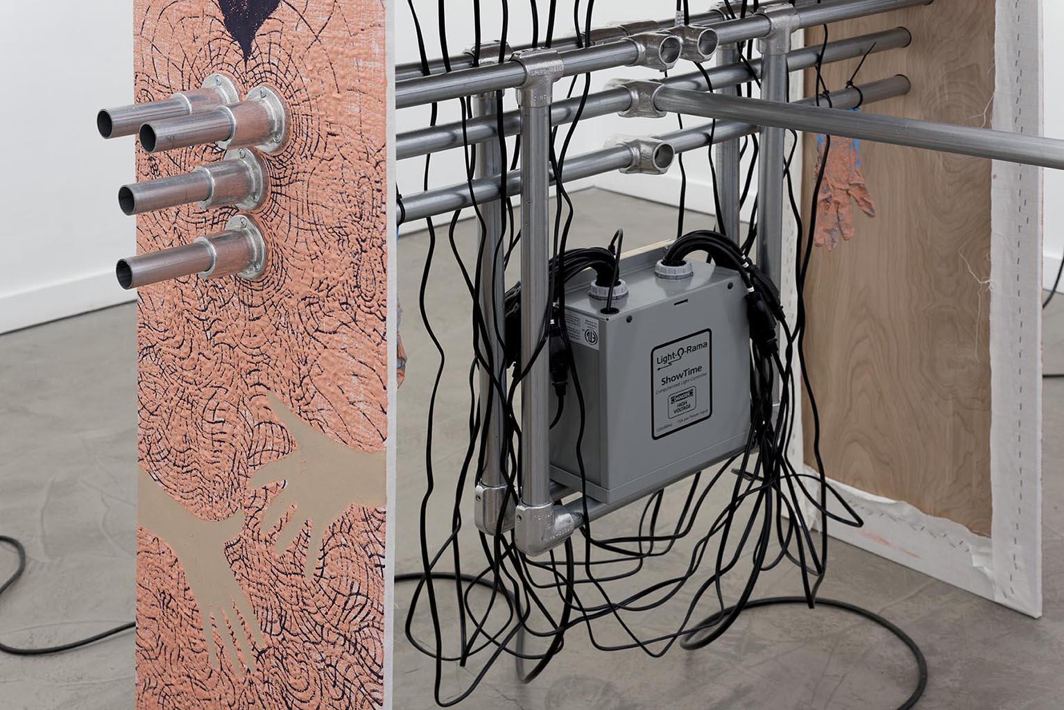 Hot Box Kid(Detail Shot), 2015, Cardboard, tape, acrylic, bleached linen, light bulbs, nitrile gloves, abraded golf balls, chain link fence post, aluminum fittings, door stoppers